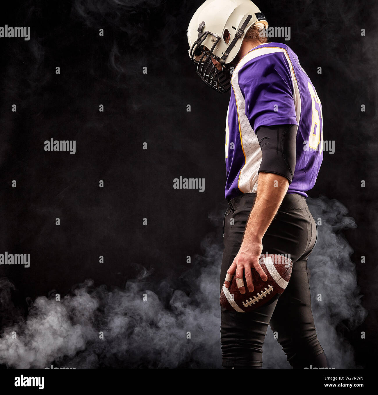 Portrait close-up, American football player, bearded without a helmet with the ball in his hands. Concept American football, patriotism, close-up. - Stock Image