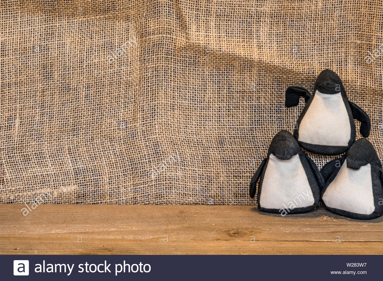 Stacked juggling penguins on a canvas backdrop - Stock Image