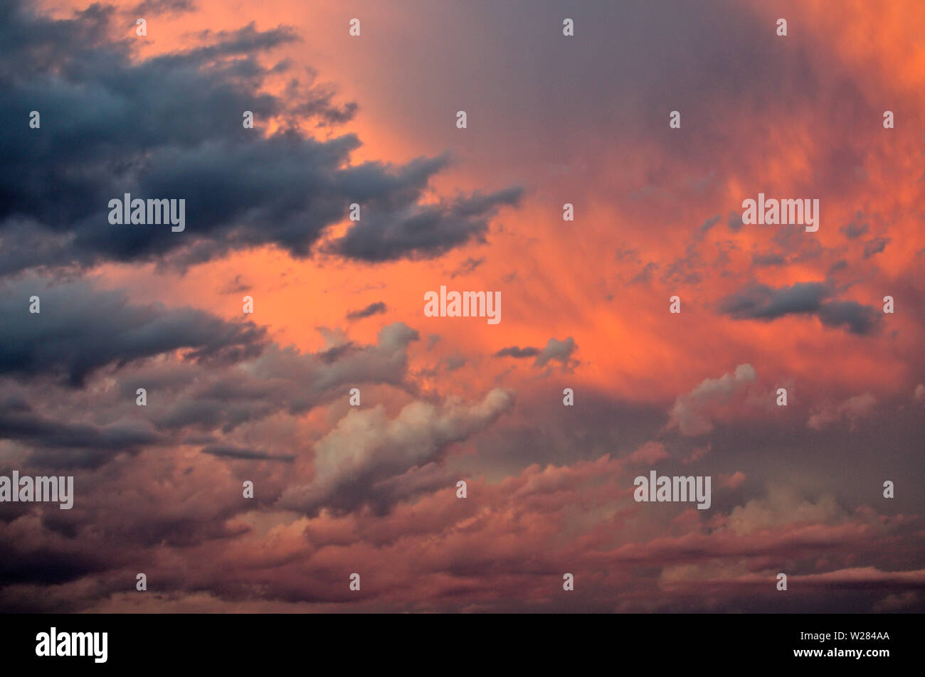Several layers of weird multicolored clouds fill the sky at dawn during a summer storm in Mendoza, Argentina. - Stock Image