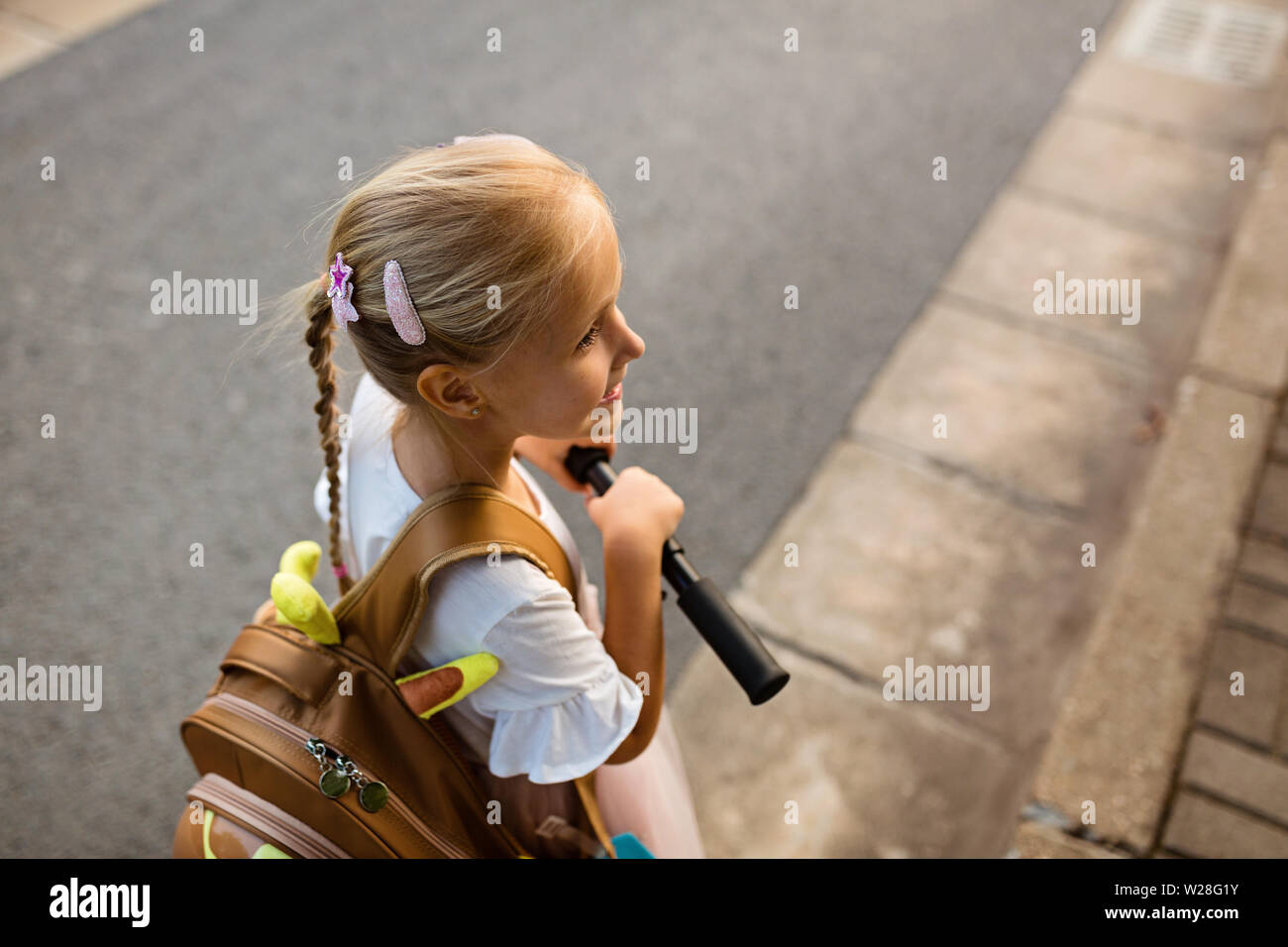 Kid girl pupil from behind walking back to home after learning study school alone with schoolbag, preschool and kindergarten education concept. First Stock Photo