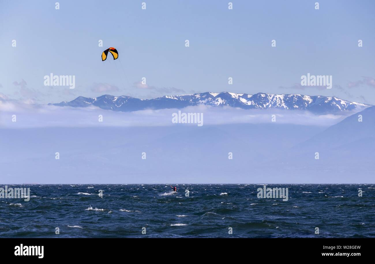 Person Windsurfing Water Waves of Juan De Fuca Strait. Windy Day, Victoria BC Canada, Distant Snowcapped Mountains, Olympic Peninsula Washington USA Stock Photo