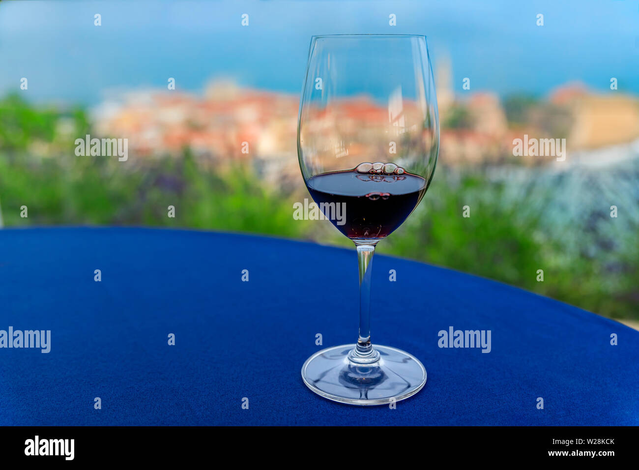 Glass of local red wine Vranac on the table at a restaurant with the Budva Old Town, and the Adriatic Sea in Montenegro blurred in the background Stock Photo