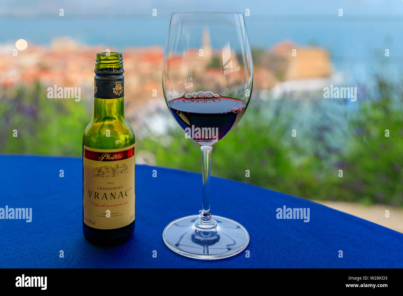Budva, Montenegro - May 27, 2019: Glass and small bottle of local red wine Vranac at a restaurant with Old Town and Adriatic Sea blurred in background Stock Photo
