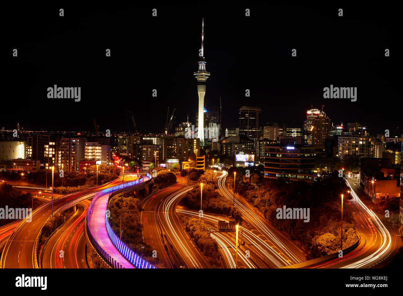 Motorways, Lightpath cycleway, and Sky Tower at night, Auckland, North Island, New Zealand - Stock Image