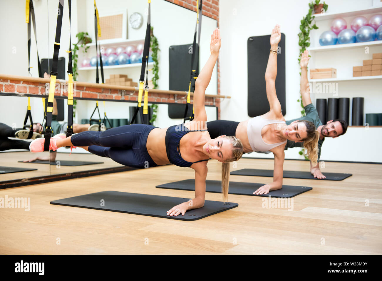 Three people exercising suspended elbow side planks using trx at gym - Stock Image
