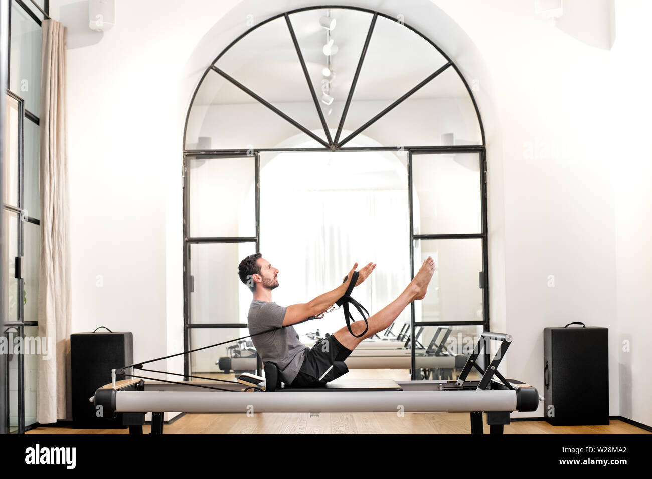 Man performing pilates teaser exercise on a reformer bed in a gym to strengthen the abdominal muscles and hip flexor in a health and fitness concept - Stock Image