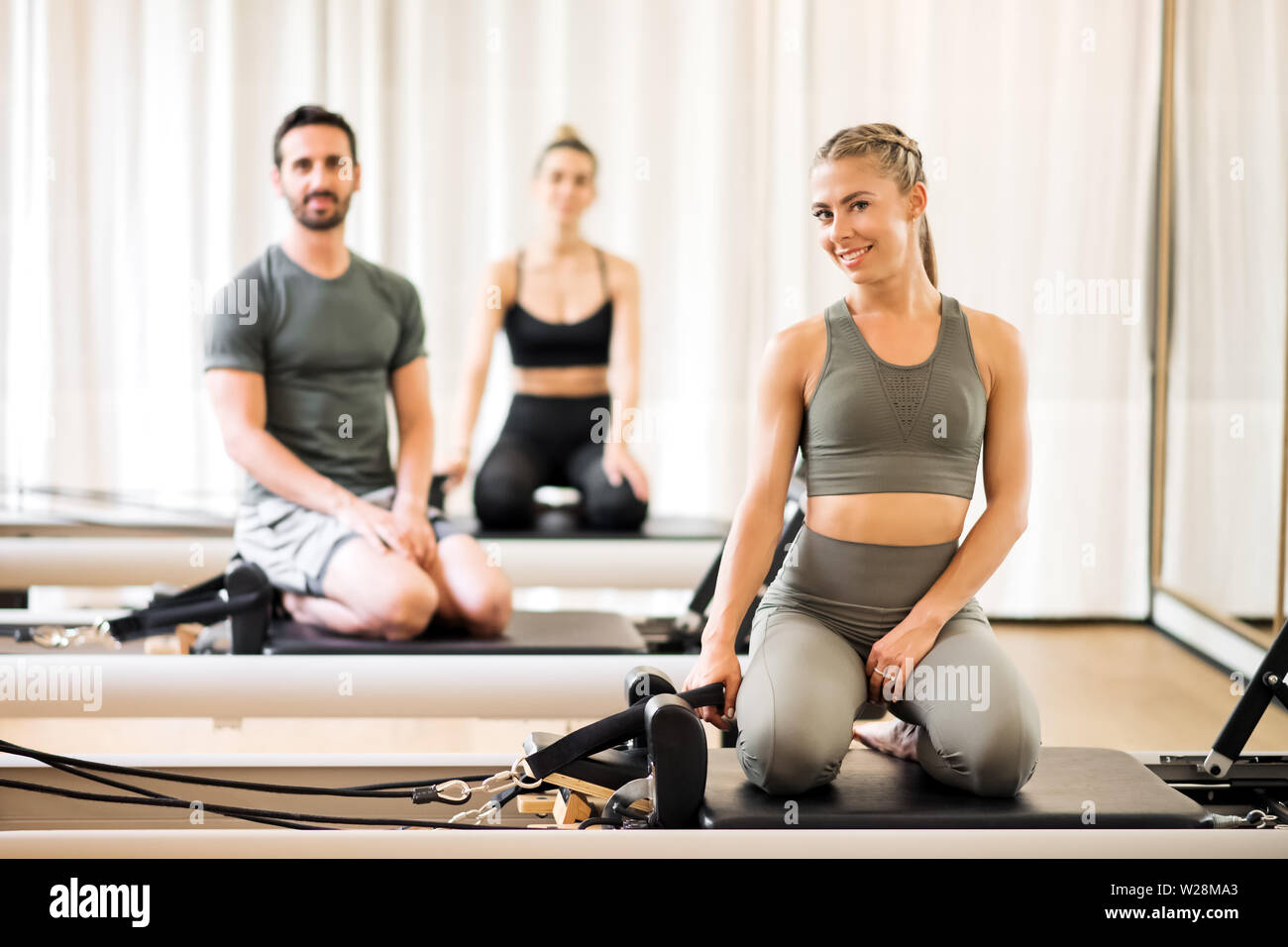 Three young athletes posing on pilates reformer beds at gym - Stock Image