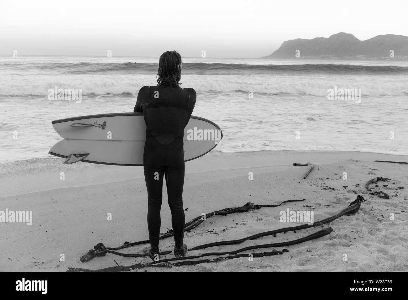 A surfer at St James on Danger Beach contemplates returning into the sea while watching another set of waves on South Africa's Cape Peninsula - Stock Image
