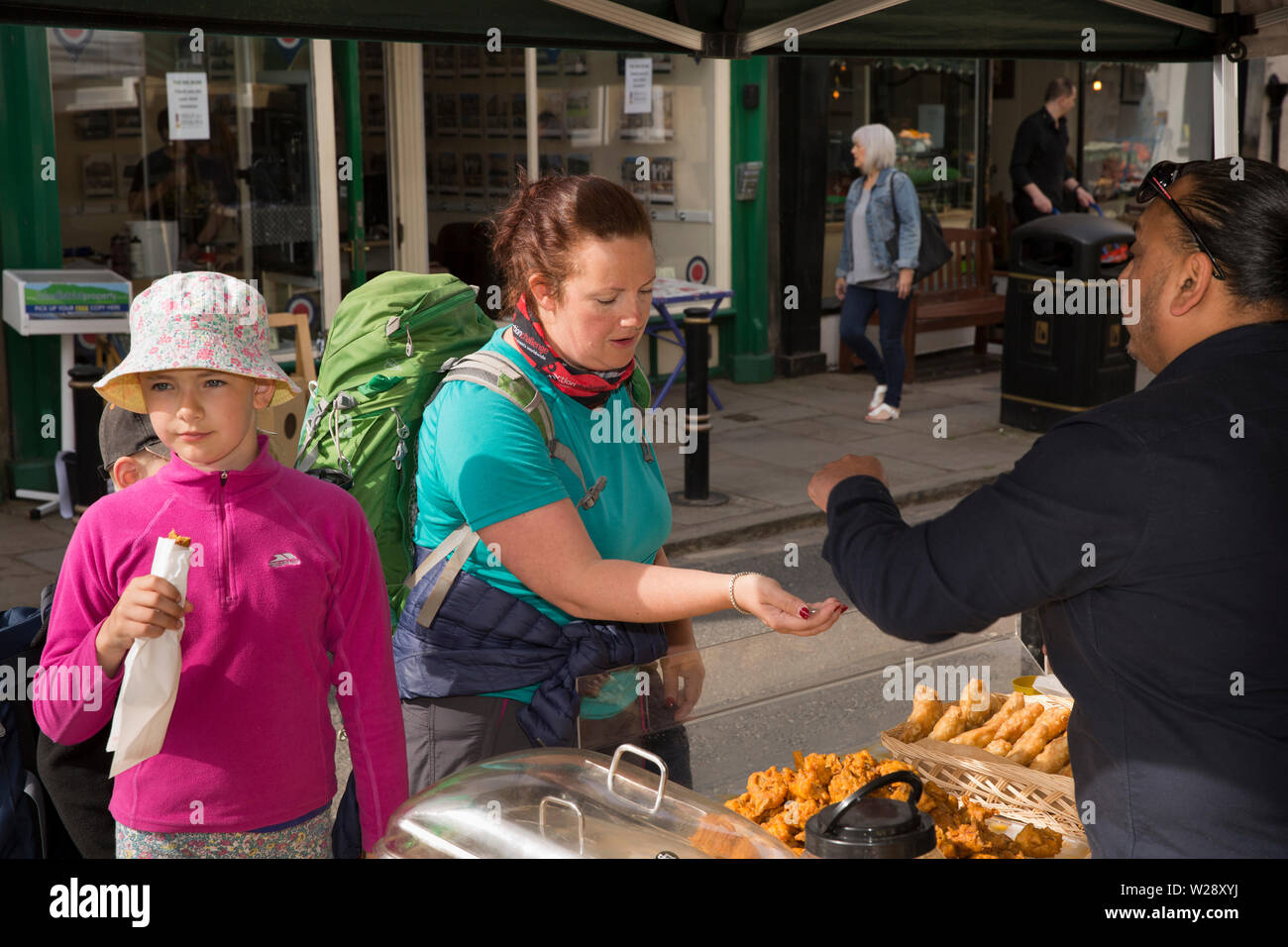 UK, Cumbria, Sedbergh, Main Street, monthly artizan's market, woman and child buying Indian takeaway food from roadside stall Stock Photo