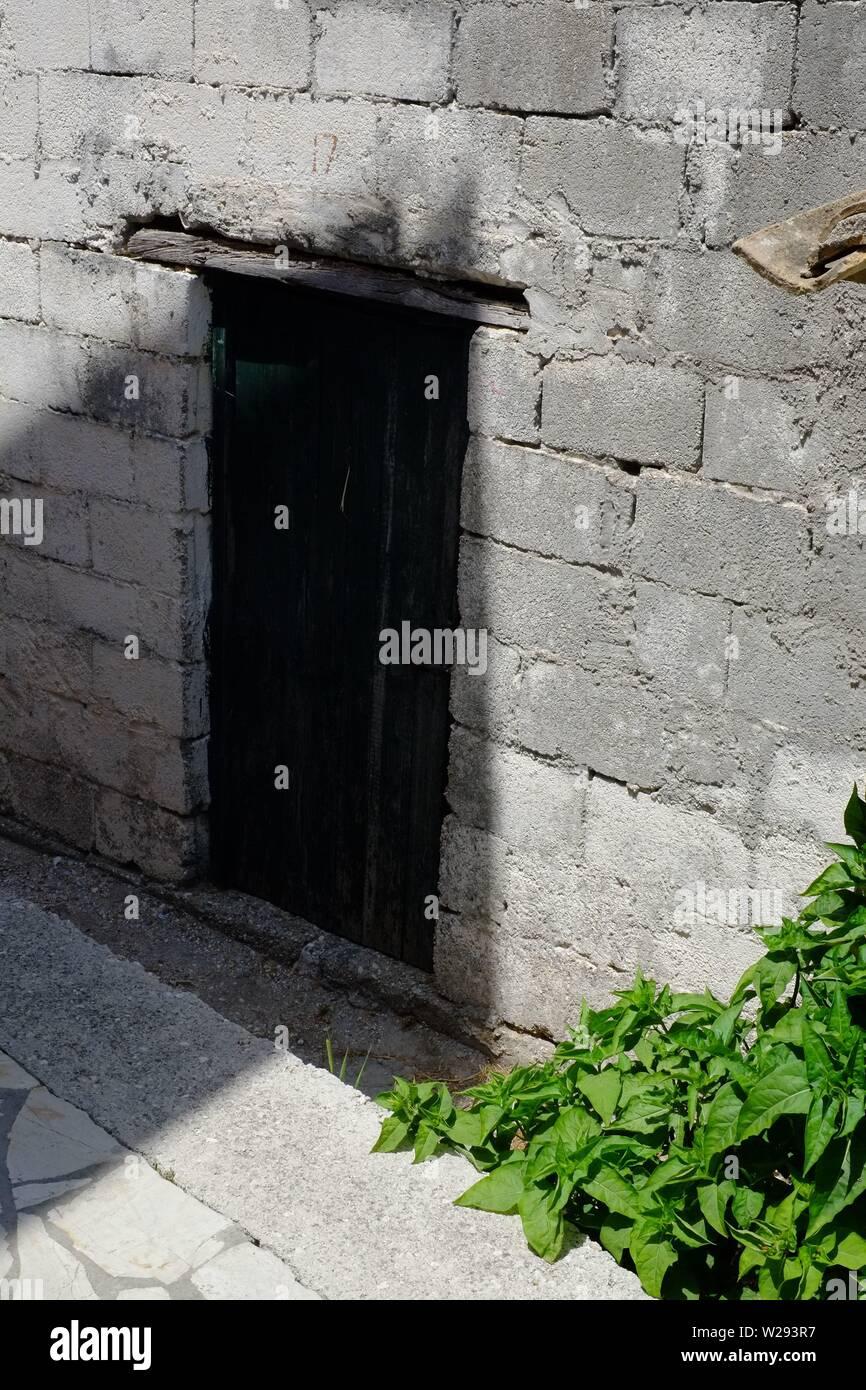 Brooding Afionis door in a dark shaded alleyway - Stock Image