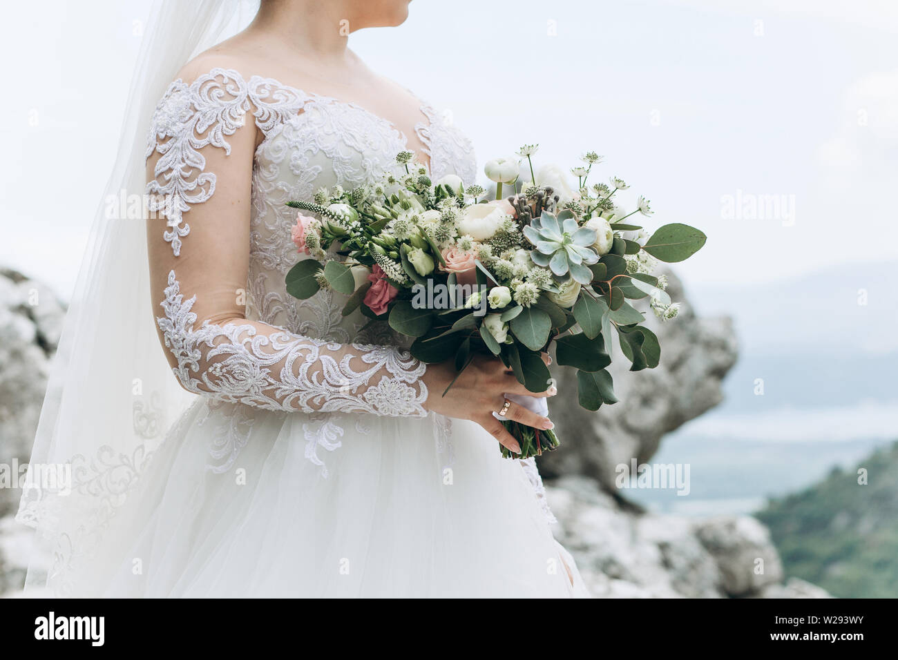 A Bride In A White Dress Is Holding A Beautiful Wedding Bouquet