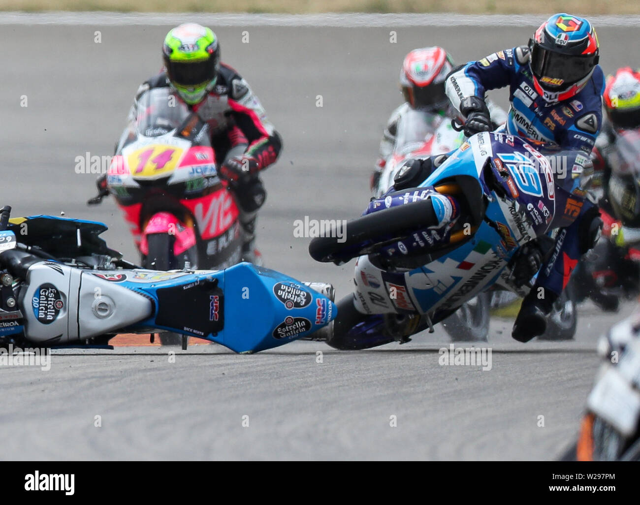 Hohenstein Ernstthal, Germany. 07th July, 2019. Motorsport/Motorcycle, Grand Prix of Germany, Moto3 at the Sachsenring: Rider Gabriel Rodrigo (Argentina, Kömmerling Gresini Moto3 Team) crashes over the bike of rider Alonso Lopez (Spain, Estrella Galicia 0, 0 Team) in the first lap after the start. Credit: Jan Woitas/dpa-Zentralbild/dpa/Alamy Live News - Stock Image