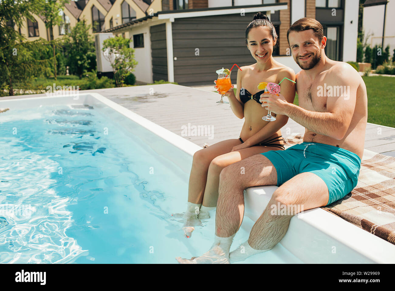 Lovely heteroseksual couple rented a house with a swimming pool. Man and woman sitting near water pool and holding fresh cocktail - Stock Image