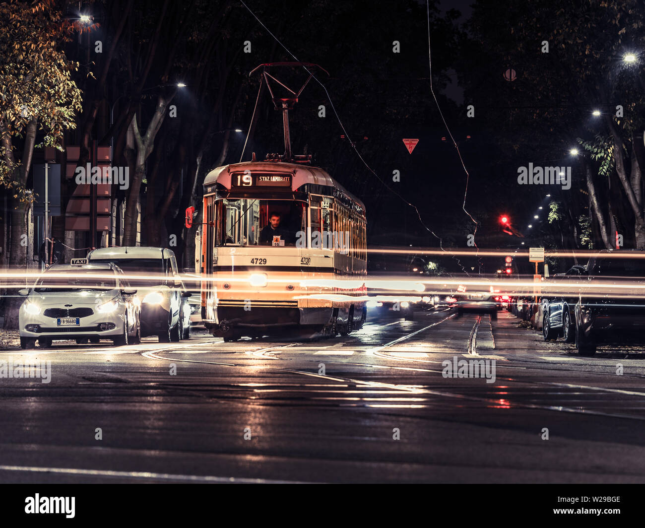 Milan, Italy, 09/11-18. A yellow tram has stopped, waiting for green light in a busy intersection. - Stock Image