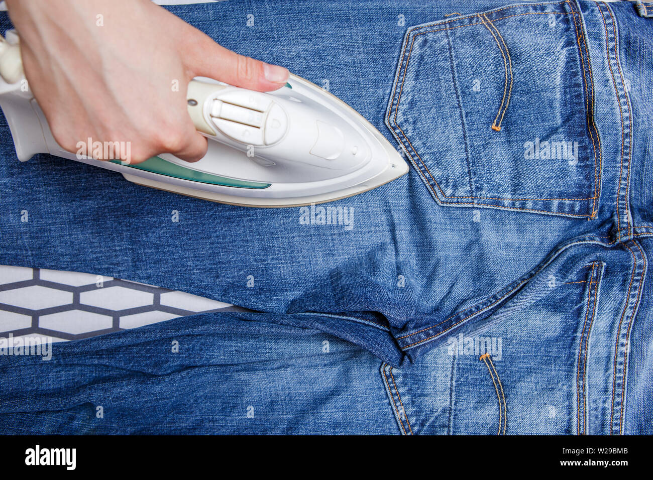 Photo of man ironing blue jeans on board - Stock Image