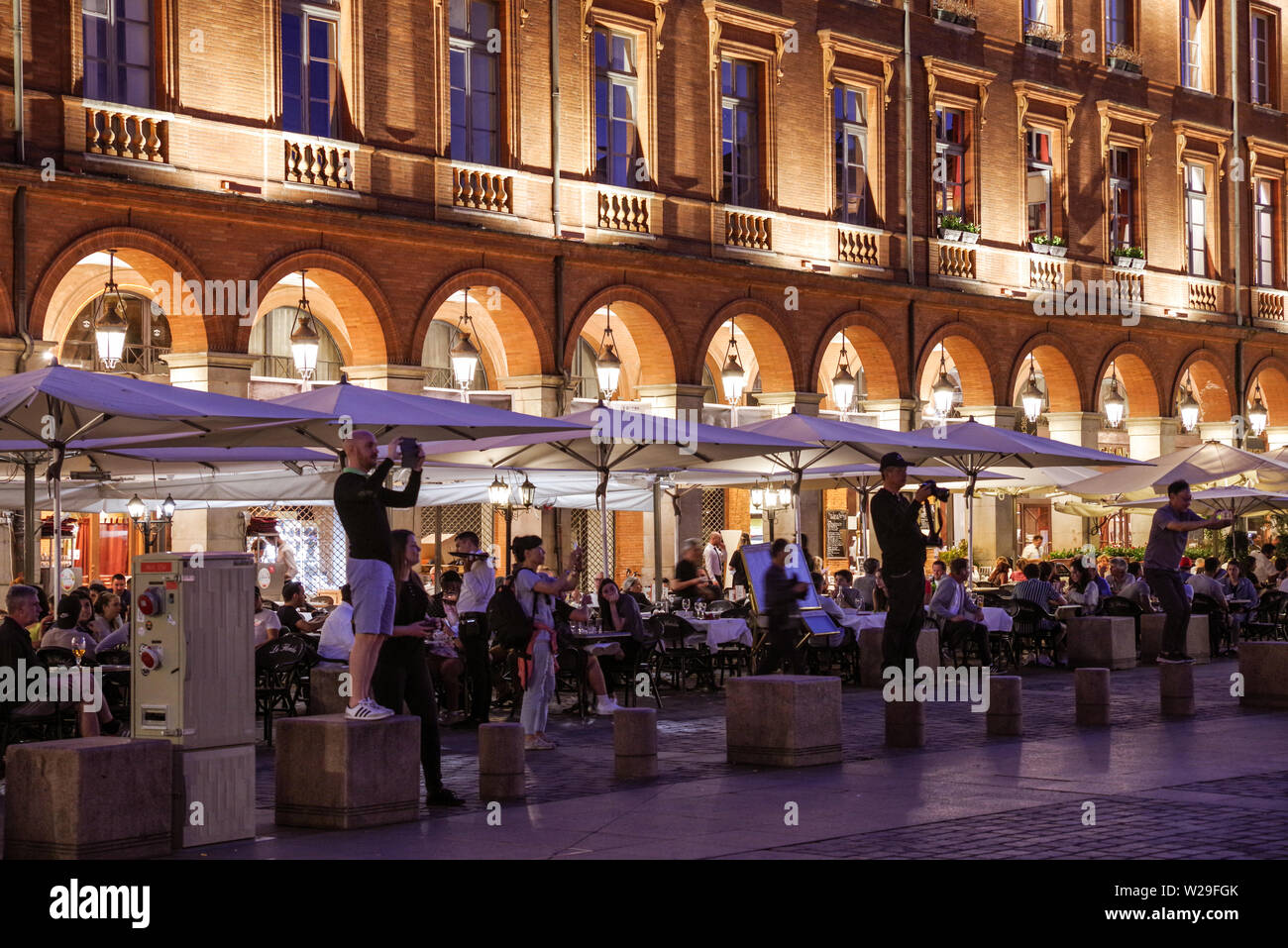Tourists taking pictures at Place du Capitole in Toulouse (France) at night - Stock Image