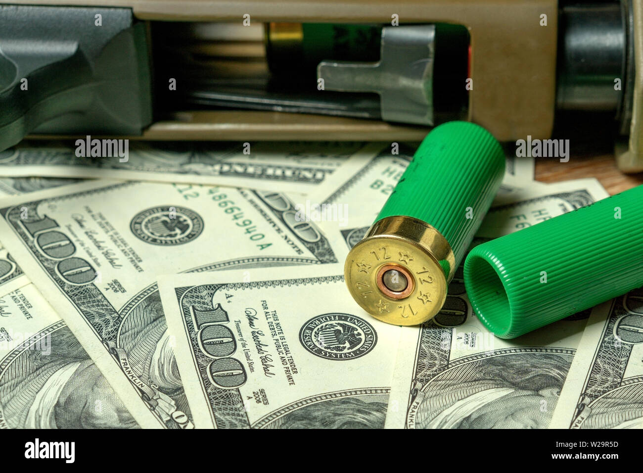 Shotgun and cartridges on dollars. Concept for crime, global arms trade, weapons sale. Illegal hunting, poaching - Stock Image