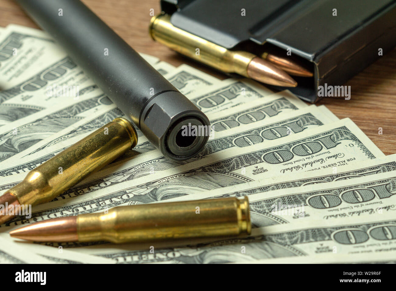 Rifle barrel, magazine and cartridges on dollars. Concept for crime, contract killing, paid assassin, terrorism, war, global arms trade, weapons sale - Stock Image