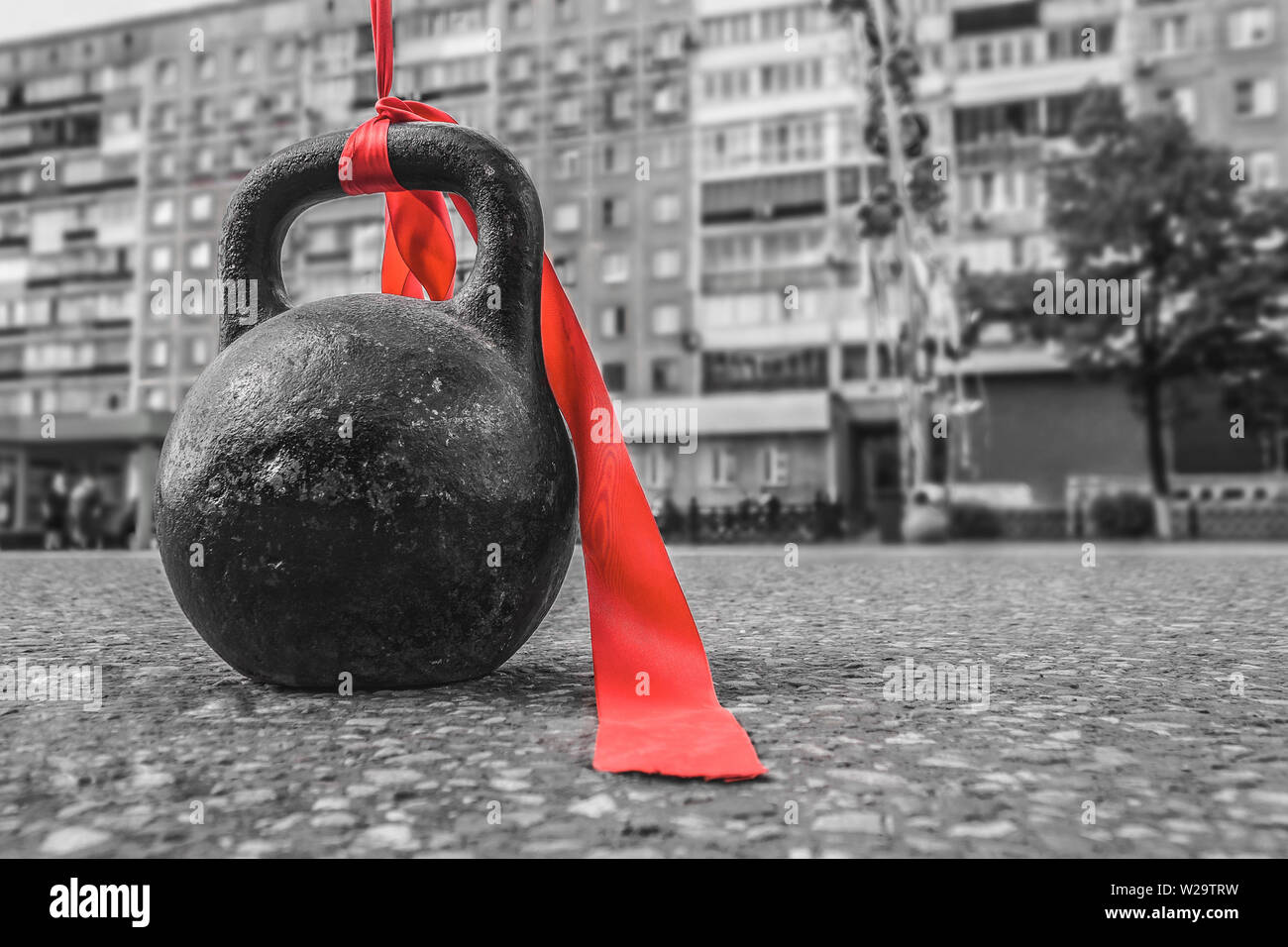 Sports equipment with a red ribbon for bodybuilding is on the asphalt during a sports holiday - Stock Image