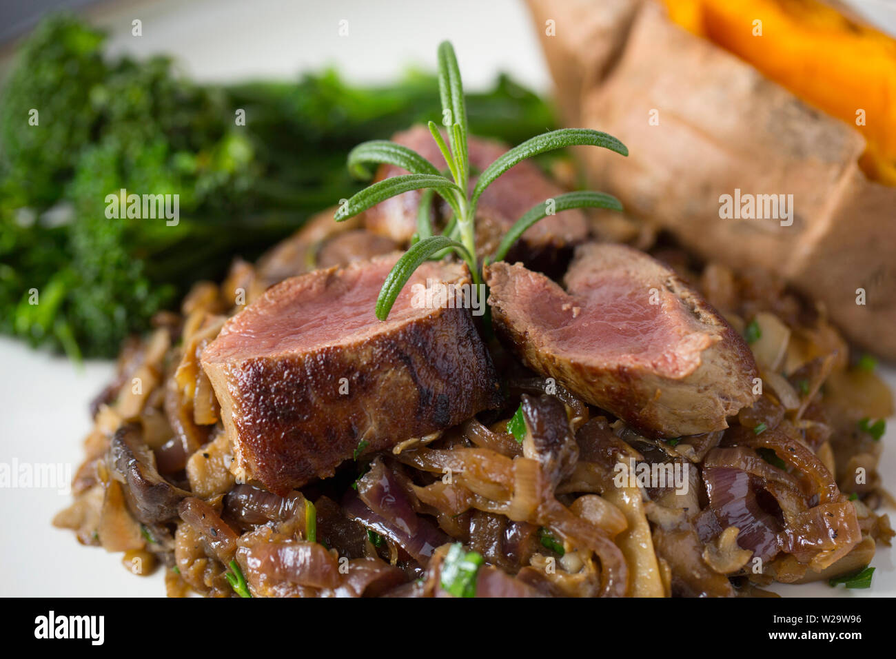 A homemade venison dish comprising of roe deer saddle fillet, or backstrap, that has been flash fried so it is still rare and sliced. It is served wit - Stock Image