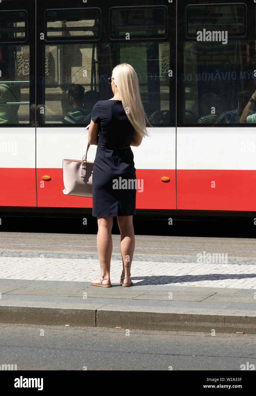 Young blond woman wearing black dress carrying a pink handbag waiting for the Tram in Prague Europe. Background tram with people in their seats. - Stock Image