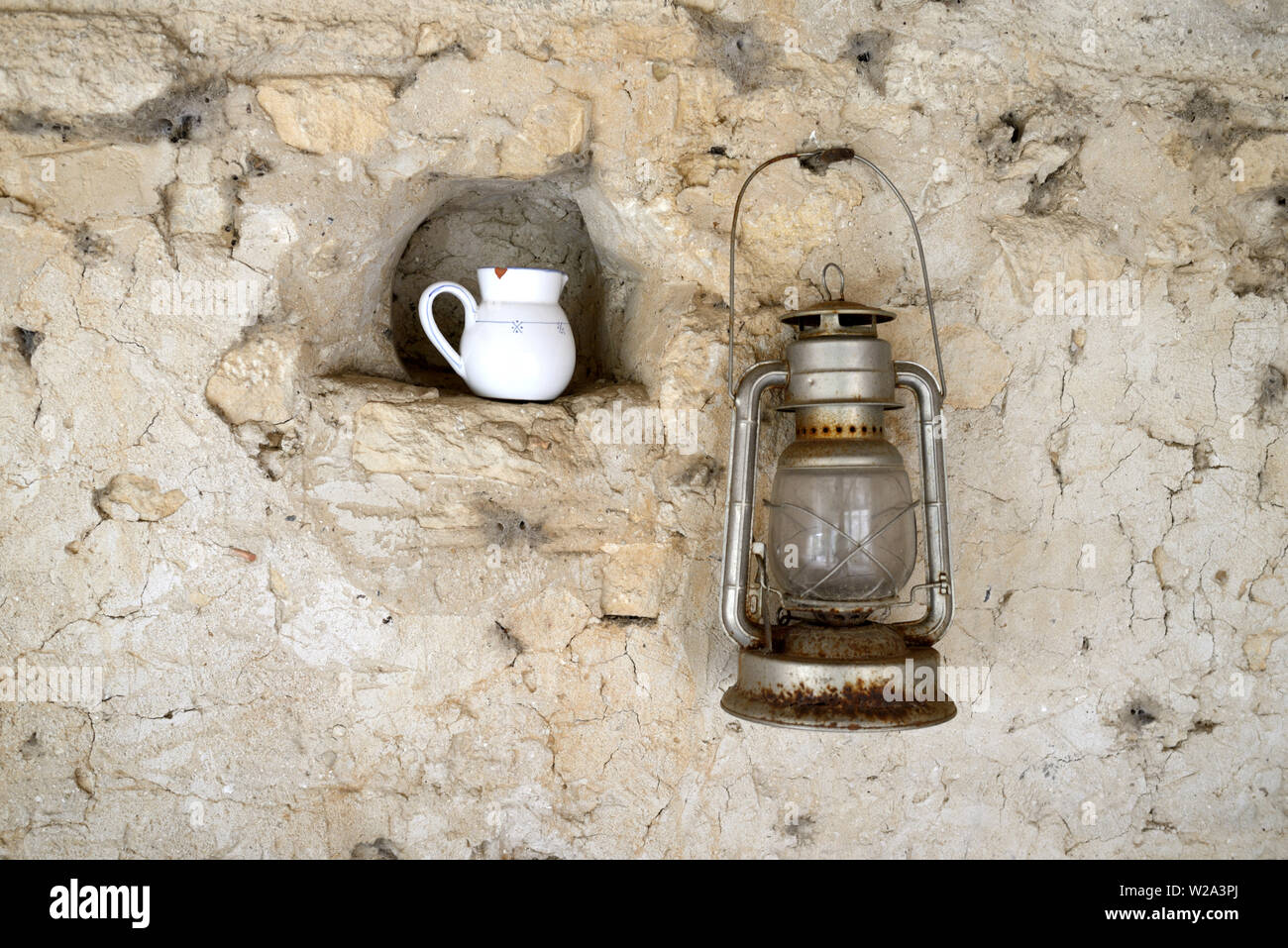 Old or Vintage Oil Lamp Hanging on Wall & Milk Jug in Niche Still Life Against Old Stone Wall - Stock Image