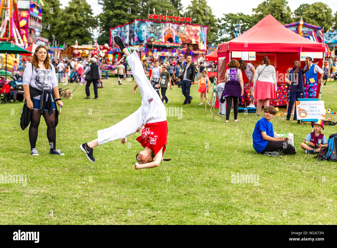 Northampton, UK. 7th July 2019. Northampton Town Show, A  young girl from the Tae Kwon-do kickboxing fitness classes doing cart wheels. Today Sunday the last day of the show the weather has greatly improved from yesterday bringing lots of people out and about. Credit: Keith J Smith./Alamy Live News - Stock Image