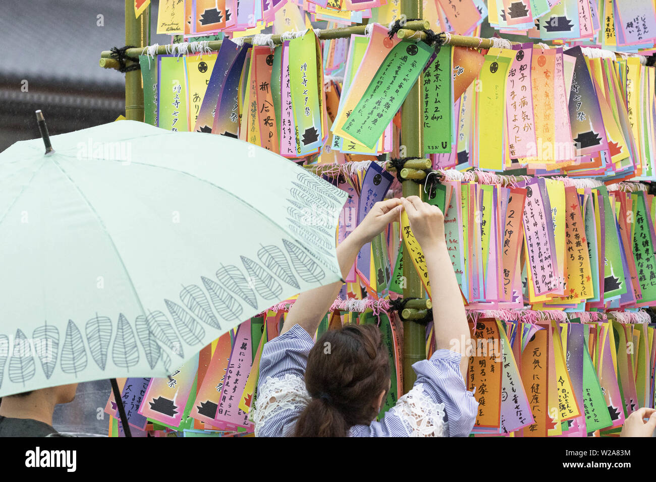 Tokyo, Japan. 7th July, 2019. Visitors hang their wishes on bamboo as part of the Tanabata festival at Zojoji Temple. Every year, people write their wishes on colorful papers (Tanzaku) to hang it on bamboo branches as a tradition of the Tanabata Festival. The annual celebration commemorates the legend of two lovers separated by the Milky Way who only meet once a year on the seventh day of the seventh month. The festival has been held since the Edo era. Credit: Rodrigo Reyes Marin/ZUMA Wire/Alamy Live News - Stock Image