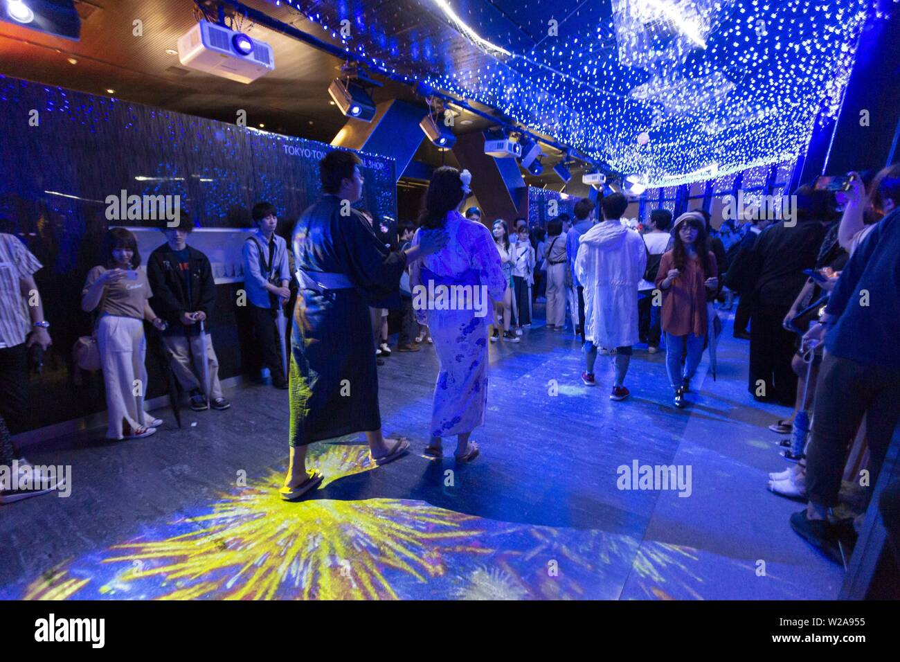 Tokyo, Japan. 7th July, 2019. Visitors wearing traditional Japanese clothes (Yukata) contemplate the LED lights simulating the Milky Way in commemoration of the festival of Tanabata at Tokyo Tower. Every year, people write their wishes on colorful papers (Tanzaku) to hang it on bamboo branches as a tradition of the Tanabata Festival. The annual celebration commemorates the legend of two lovers separated by the Milky Way who only meet once a year on the seventh day of the seventh month. The festival has been held since the Edo era. Credit: Rodrigo Reyes Marin/ZUMA Wire/Alamy Live News - Stock Image