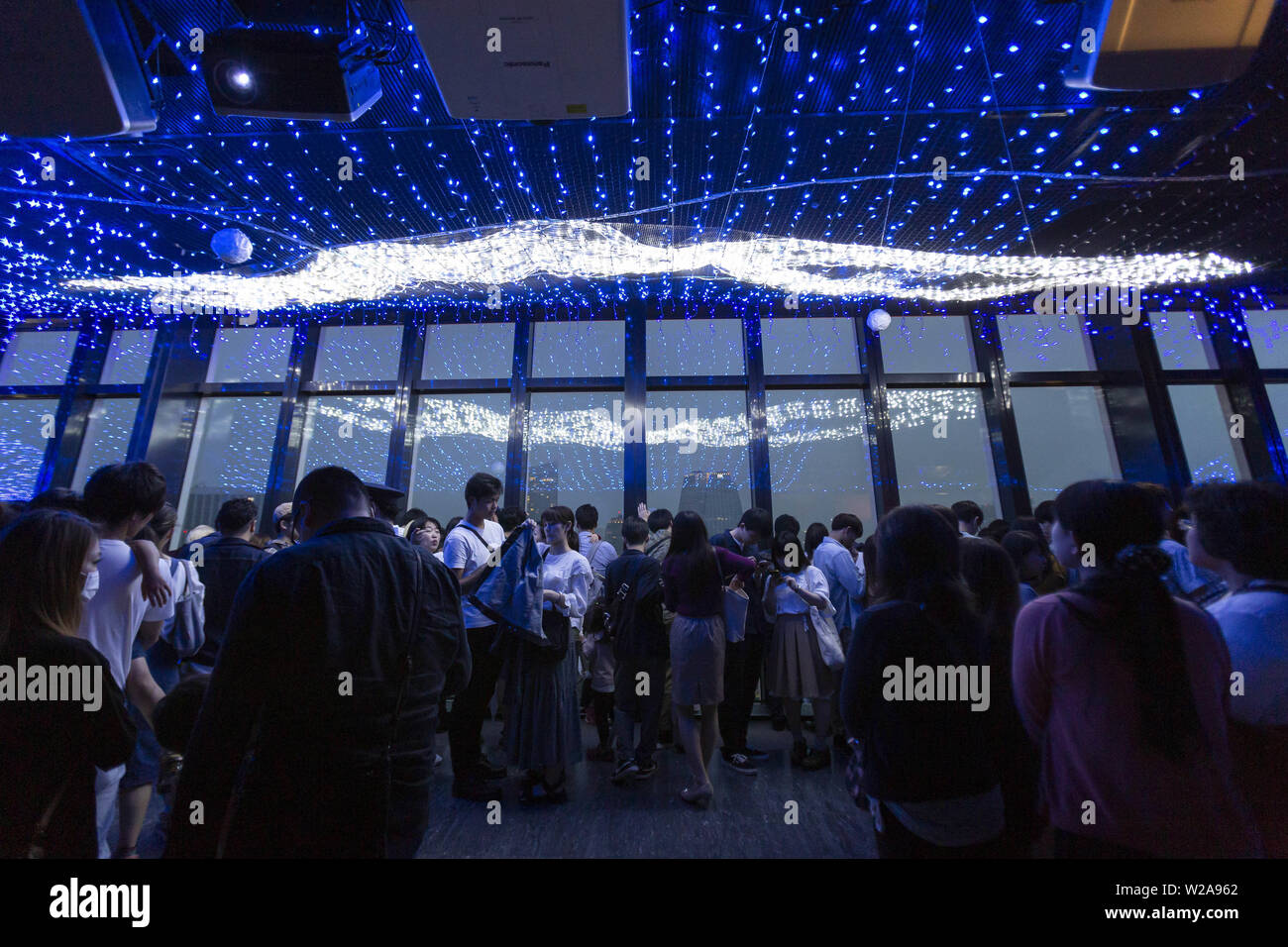 Tokyo, Japan. 7th July, 2019. Visitors contemplate the LED lights simulating the Milky Way in commemoration of the festival of Tanabata at Tokyo Tower. Every year, people write their wishes on colorful papers (Tanzaku) to hang it on bamboo branches as a tradition of the Tanabata Festival. The annual celebration commemorates the legend of two lovers separated by the Milky Way who only meet once a year on the seventh day of the seventh month. The festival has been held since the Edo era. Credit: Rodrigo Reyes Marin/ZUMA Wire/Alamy Live News - Stock Image