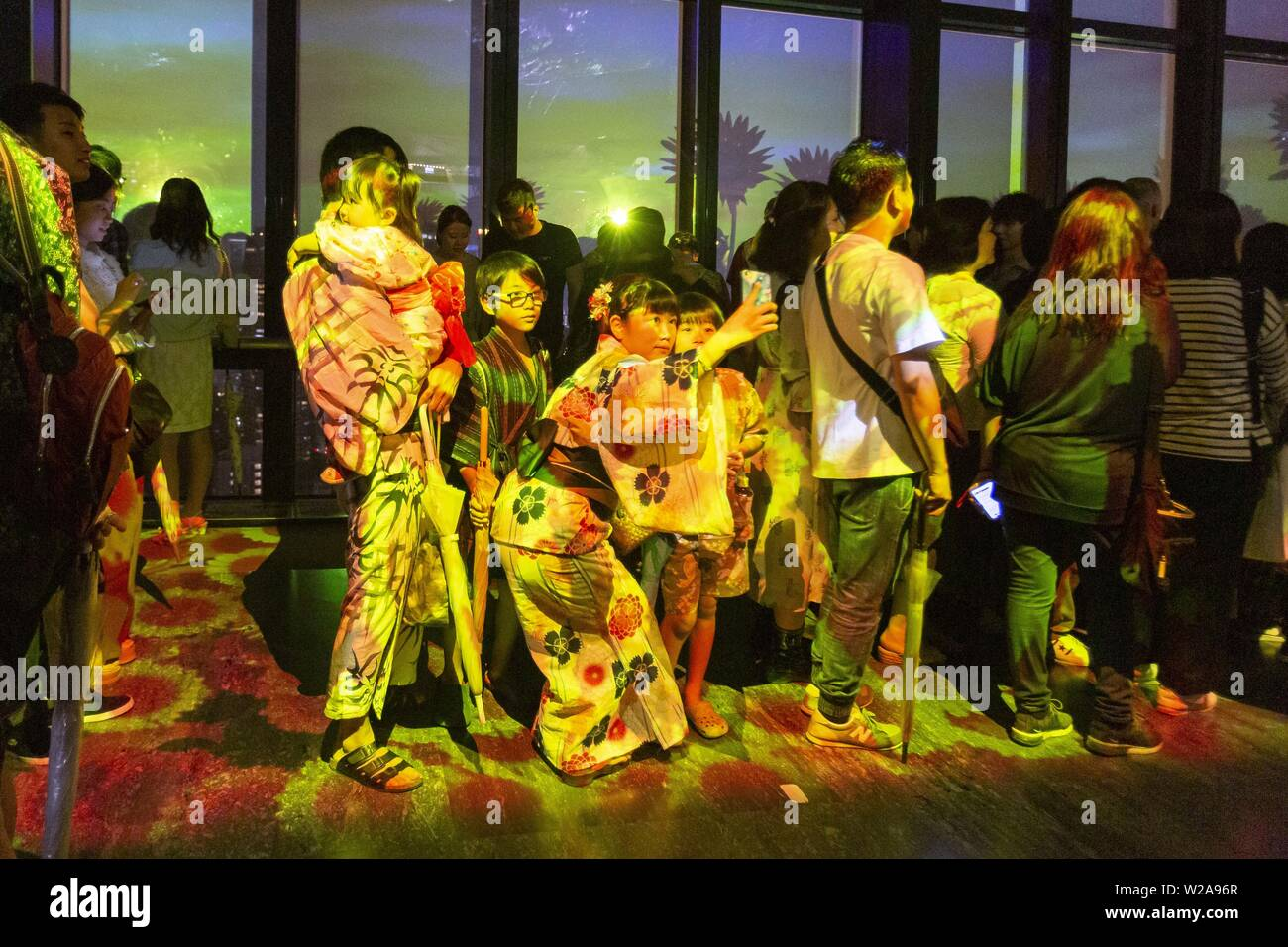 Tokyo, Japan. 7th July, 2019. Visitors wearing traditional Japanese clothes (Yukata) enjoy the illumination City Light Fantasia in commemoration of the festival of Tanabata at Tokyo Tower. Every year, people write their wishes on colorful papers (Tanzaku) to hang it on bamboo branches as a tradition of the Tanabata Festival. The annual celebration commemorates the legend of two lovers separated by the Milky Way who only meet once a year on the seventh day of the seventh month. The festival has been held since the Edo era. Credit: Rodrigo Reyes Marin/ZUMA Wire/Alamy Live News - Stock Image