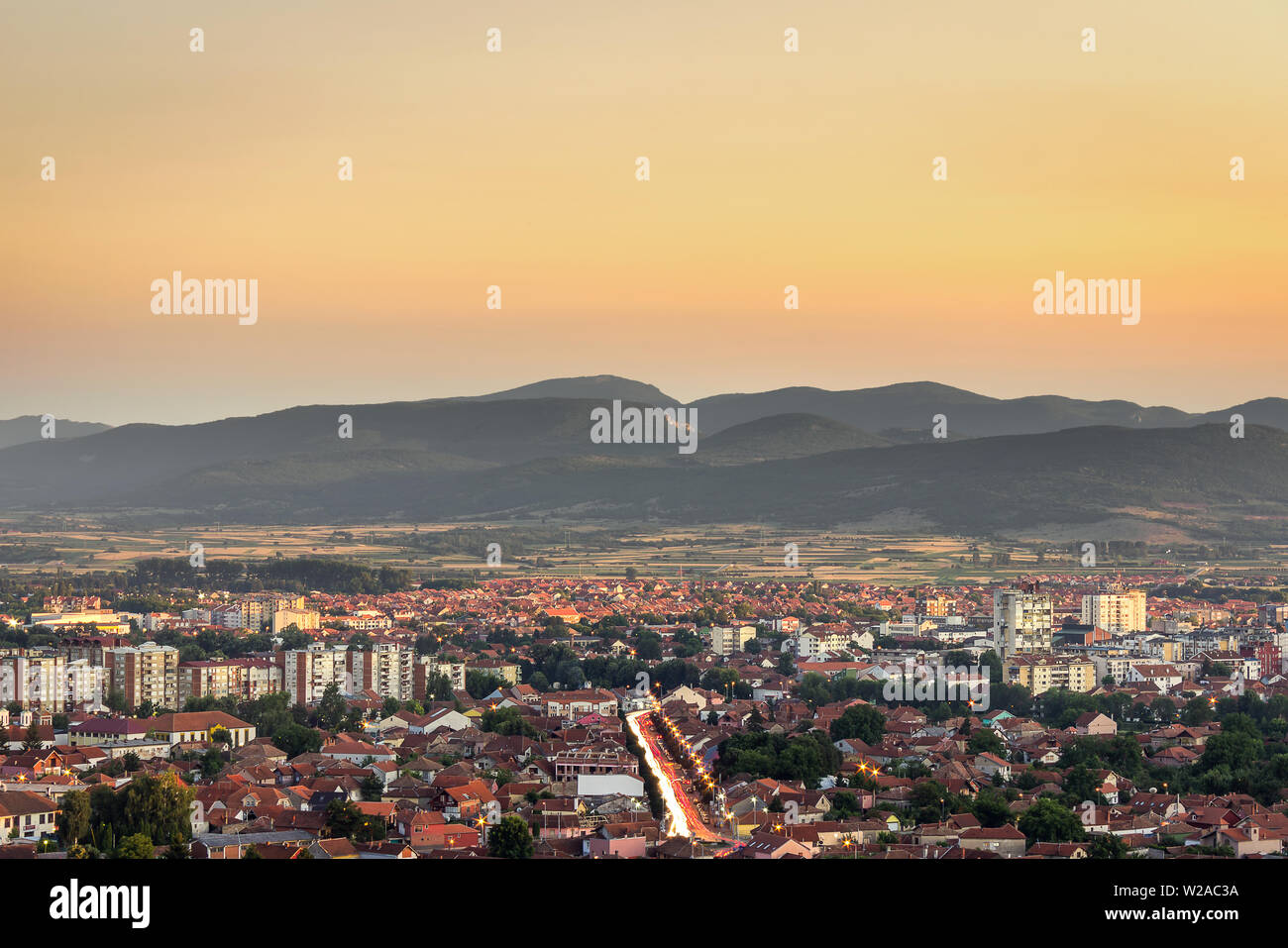 Beautiful golden hour sky above Pirot cityscape with buildings lighten by setting sun, city lights and car trails - Stock Image