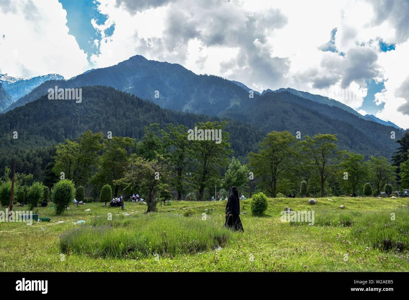 Kashmir, India  07th July, 2019  A Kashmiri burqa-clad woman walks