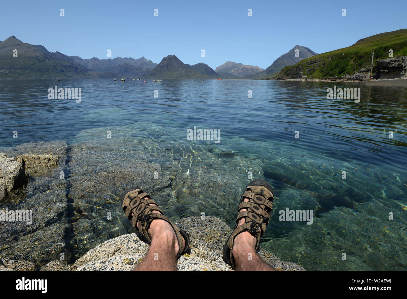 View from Elgol over Loch Skavaig to the Cuillin Hills with feet hanging over water - Stock Image
