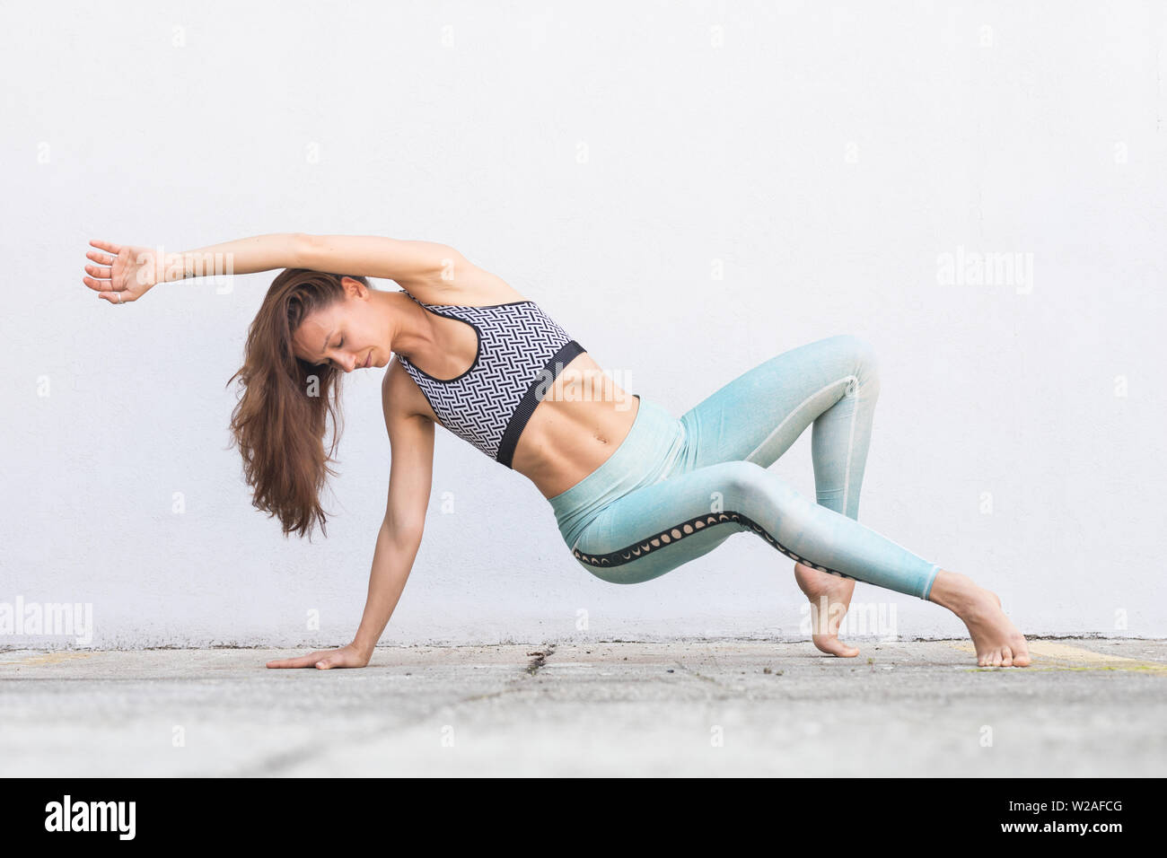 Fit sporty active girl in fashion sportswear doing yoga fitness exercise in front of gray wall, outdoor sports, urban style Stock Photo