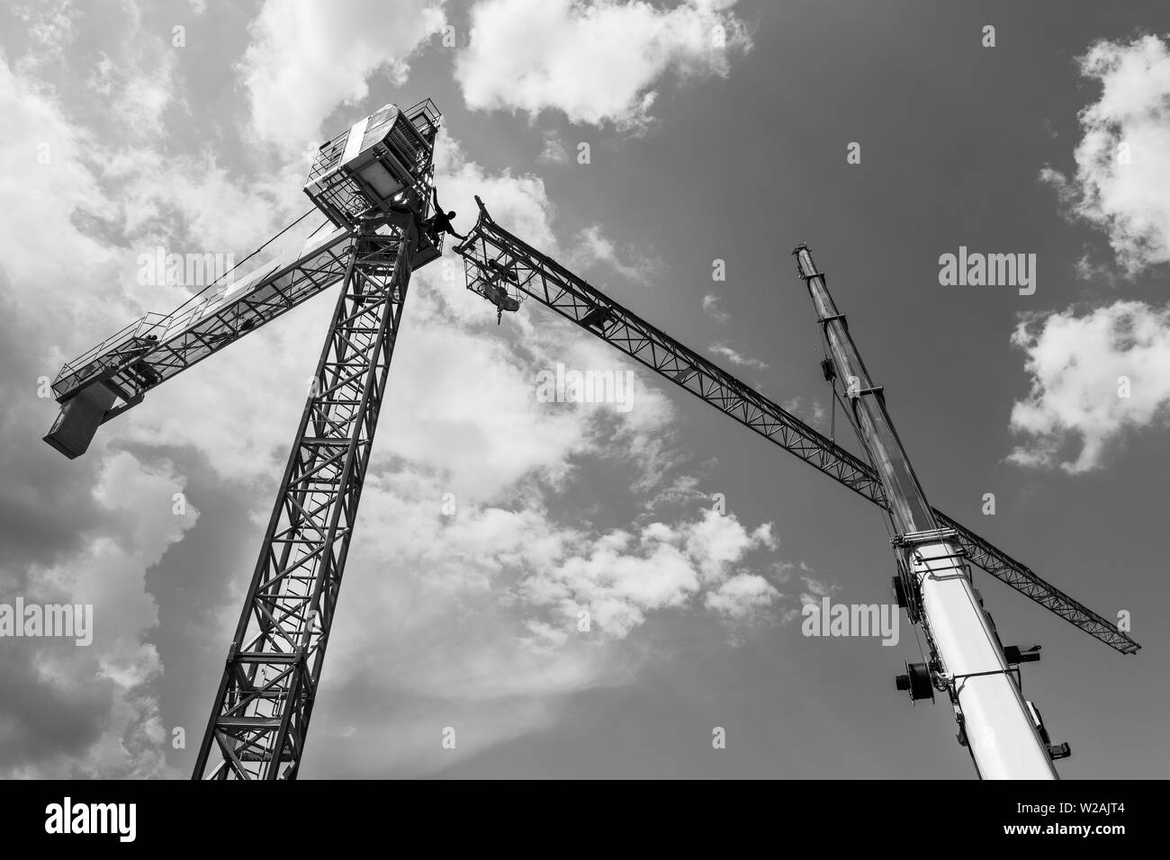 Tower crane installation. Black and white silhouette. Work at heights. Artistic construction background. Telescopic boom of lifting device. Cloudy sky. - Stock Image