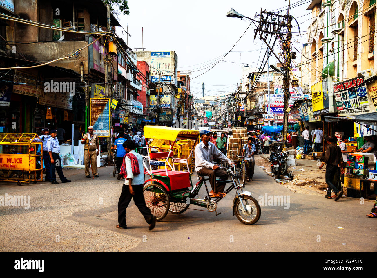 DELHI, INDIA - JULY 6, 2016: Busy car traffic in the city center of Delhi, India. Various shops, restaurants and cafes. Numerous signs, car traffic an - Stock Image