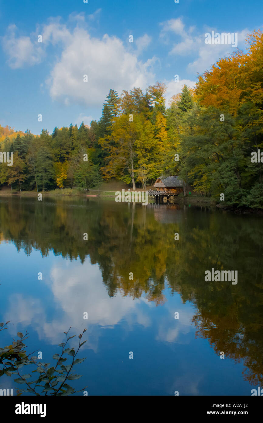 Lake and reflection in a lake showing forest and cabin. Lake is Trakoscan lake near castle Trakoscan in north-west Croatia. - Stock Image