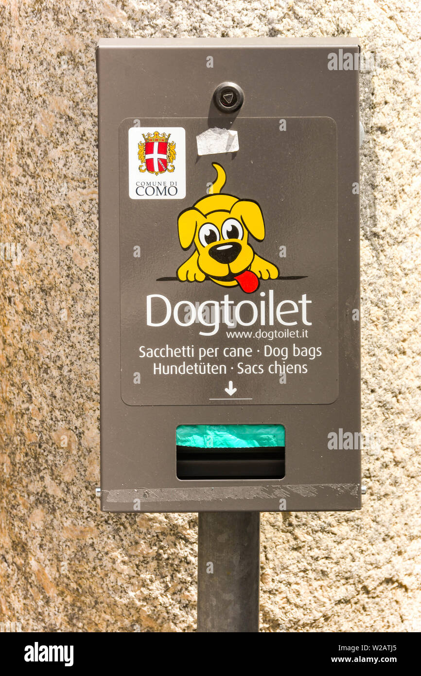 LAKE COMO, ITALY - JUNE 2019: Sign showing a toilet for dogs and holding a dispenser for pet owners to pick up dog waste. - Stock Image