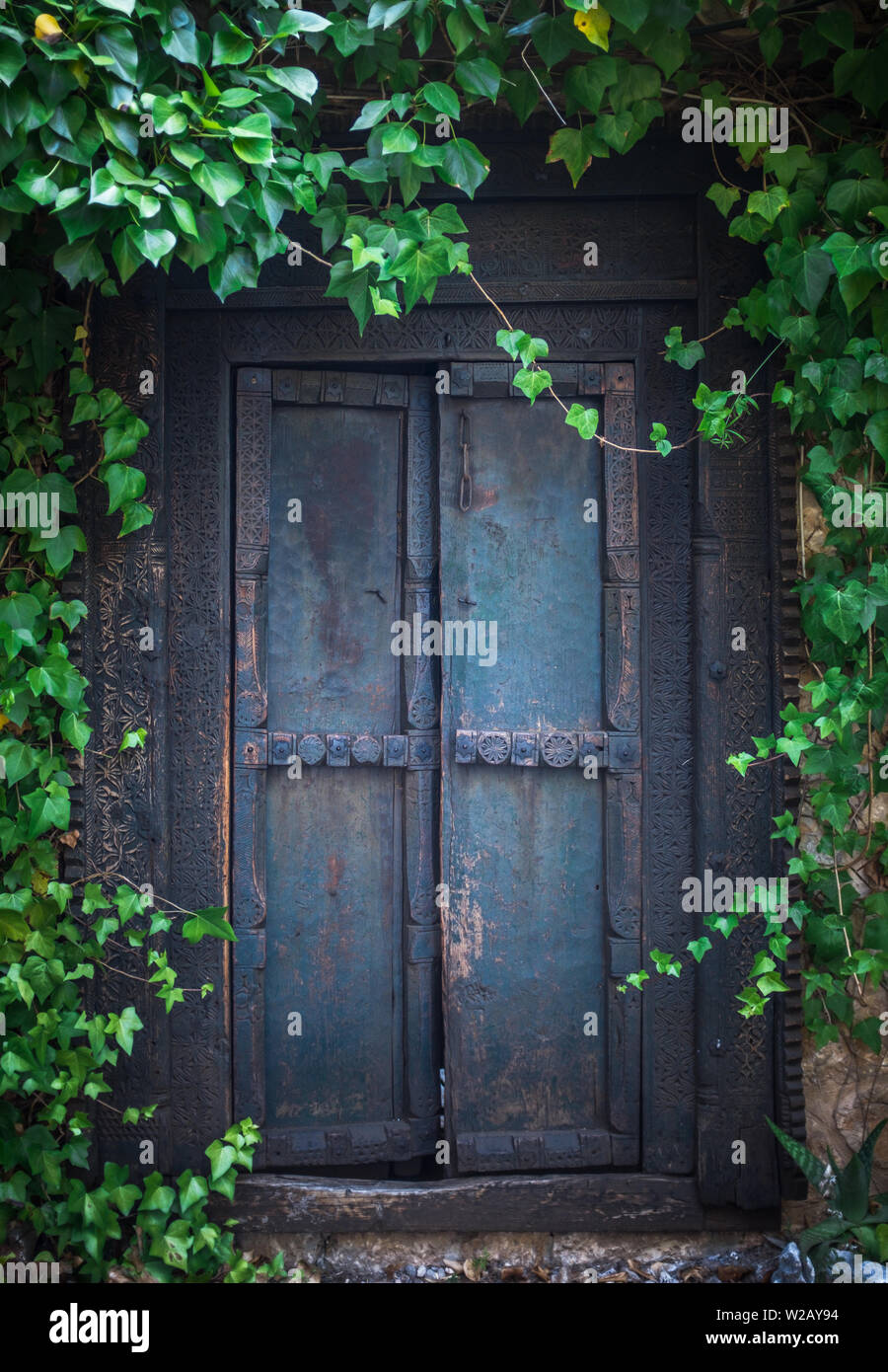 Ivy Surrounding An Old Wooden Door To A Secret Garden At An Old Mansion House Stock Photo