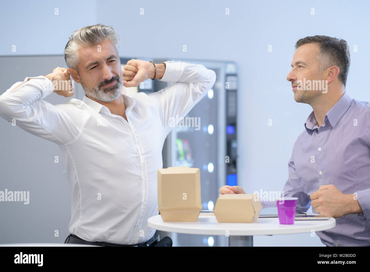 businessmen with takeaway fast-food cartons one stretching - Stock Image