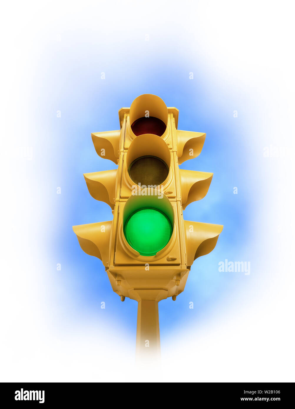 Upward view of tall vintage yellow traffic signal with green light on white vignette background - Stock Image