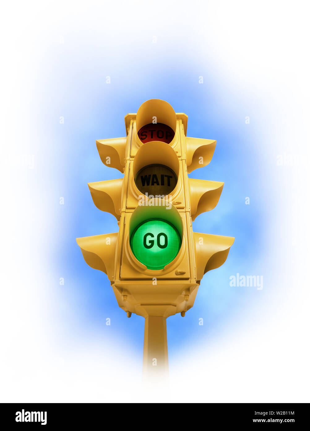 Upward view of  tall vintage yellow traffic signal with green GO light on white vignette background Stock Photo