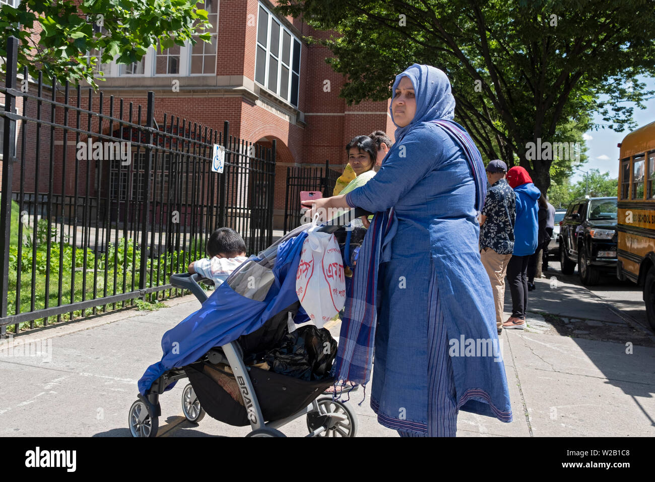 A Muslim woman in a hijab and ethnic clothing waits for her child outside a school, PS69, in Jackson Heights, Queens, New York City. - Stock Image
