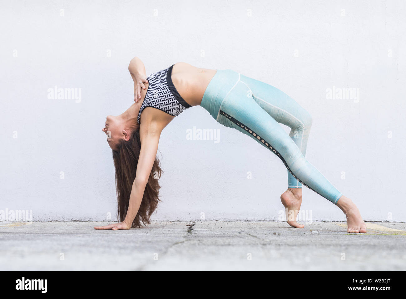 Fit sporty active girl in fashion sportswear doing yoga fitness exercise in front of gray wall, outdoor sports, urban style - Stock Image