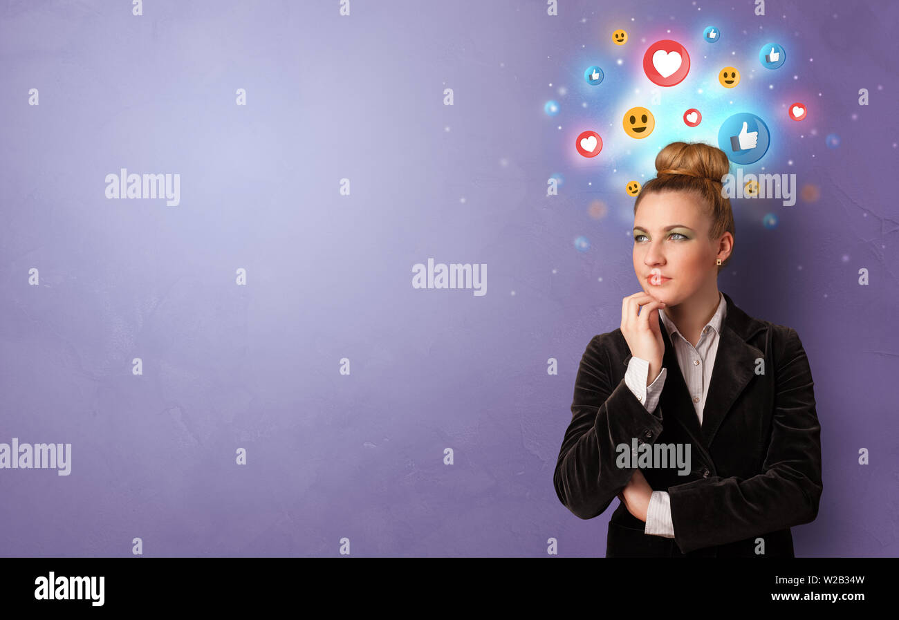 Business person standing with social media and emoticons concept - Stock Image