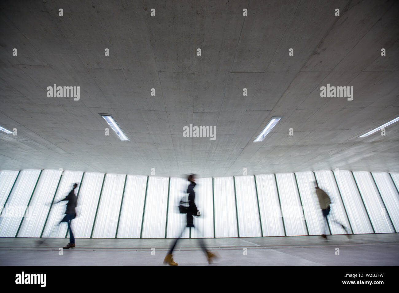 Motion blurred people - figures in an underpassage getting to their workplace in the morning. Busy city business life. - Stock Image