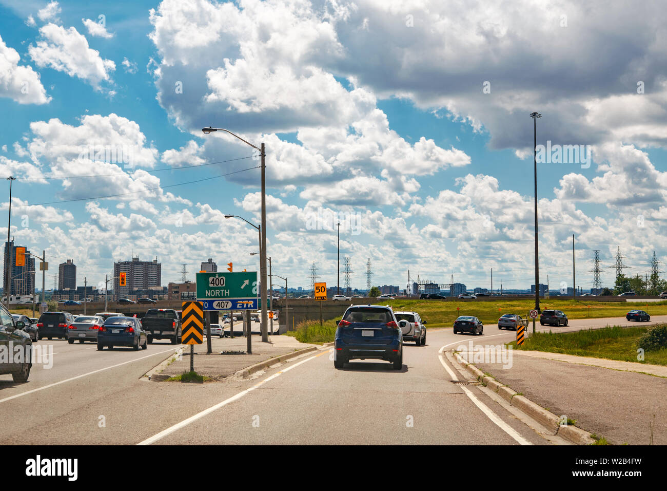 Beautiful landscape midday view of Toronto city highway street with cars traffic during sunny day with white clouds in blue sky. Busy outdoor downtown - Stock Image