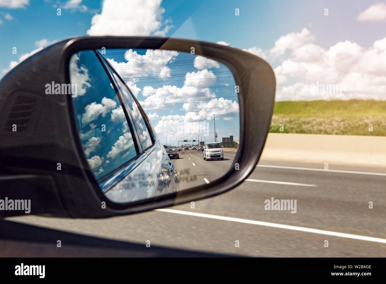 Closeup of rear back car mirror with beautiful landscape midday view of  Toronto city highway street road. Cars traffic during sunny day with white cl - Stock Image