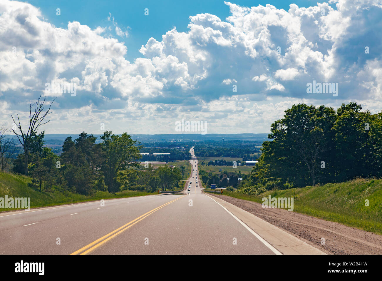 Beautiful landscape midday view of Canadian Ontario country side road with cars traffic during sunny day with white clouds in blue sky. Busy outdoor c - Stock Image